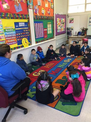 students in classroom sitting on rug on floor - teacher on chair - colorful art on the walls