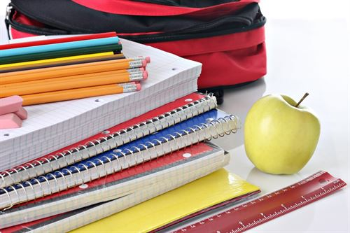 stack of notebooks and pencils with apple, ruler and bag